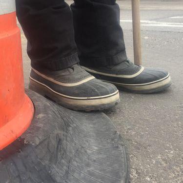shoes beside an orange traffic cone